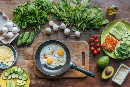 Photo for Top view of fried eggs in frying pan on cutting board and arranged fresh vegetables for healthy breakfast on wooden surface - Royalty Free Image