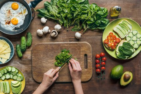 Photo for Partial view of woman cooking healthy breakfast with vegetables and toasts - Royalty Free Image