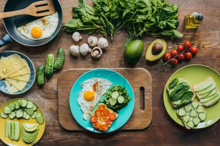 Photo for Top view of healthy breakfast on plate and arranged ingredients around on wooden surface - Royalty Free Image