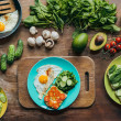 Top view of healthy breakfast on plate and arranged ingredients around on wooden surface