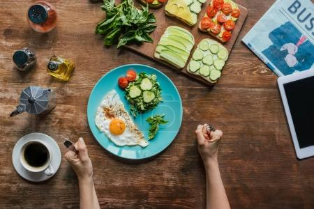 Photo for Partial view of woman having healthy breakfast with fried egg and fresh vegetables - Royalty Free Image