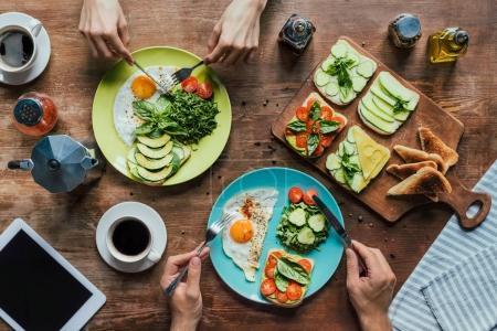 Photo pour Recadrée tir du couple petit-déjeuner sain avec légumes et toasts - image libre de droit