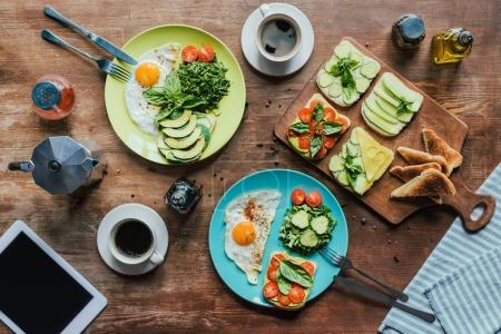 Photo for Flat lay with healthy breakfast for two with fried eggs, toasts, vegetables and cups of coffee on wooden tabletop - Royalty Free Image