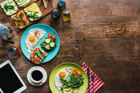 Photo for Flat lay with healthy breakfast for two with fried eggs, toasts, vegetables and cup of coffee on wooden tabletop - Royalty Free Image
