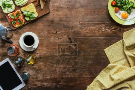 Photo for Top view of cup of coffee, tablet, tablecloth and breakfast on wooden tabletop - Royalty Free Image