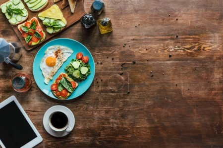 Photo for Flat lay with healthy breakfast on plate, cup of coffee and tablet on wooden tabletop - Royalty Free Image