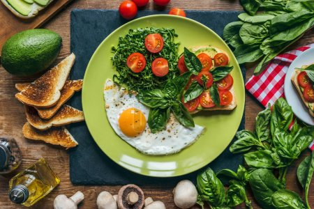 Photo for Top view of healthy breakfast with fried egg, toast and vegetables on plate - Royalty Free Image