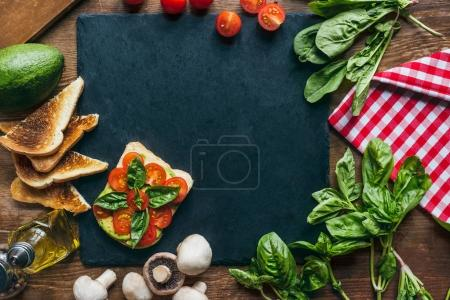 Photo for Top view of arranged fresh vegetables, avocado and toasts on wooden tabletop - Royalty Free Image