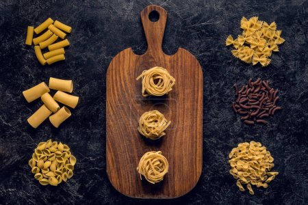 Photo for Composition of various raw pasta and wooden cutting board - Royalty Free Image