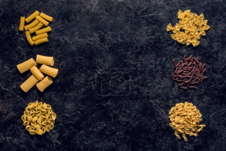 Photo for Top view of frame of various raw pasta on black concrete table - Royalty Free Image