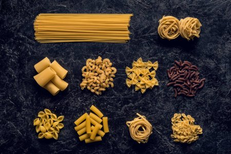Photo for Top view composition of various raw pasta on black concrete table - Royalty Free Image