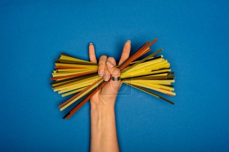Photo for Woman holding raw spaghetti and showing rock sign - Royalty Free Image