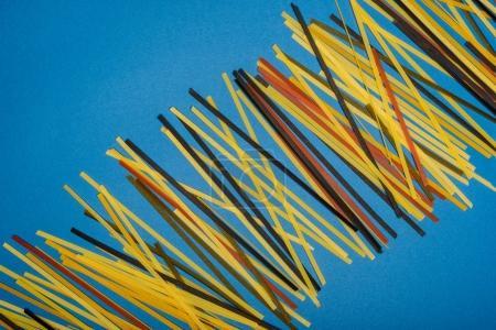 Photo pour Composition de spaghettis colorés crus sur bleu - image libre de droit