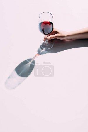 Photo pour Recadrée tir de femme tenant le verre de vin rouge sur le dessus de table rose - image libre de droit