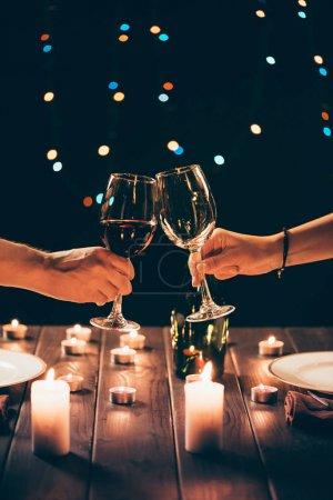 Photo pour Plan recadré de l'homme et la femme cliquetis verres avec du vin sur la table avec des bougies allumées - image libre de droit