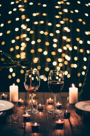 Photo for Cropped shot of person pouring wine into two glasses on served wooden table surrounded by lit candles - Royalty Free Image