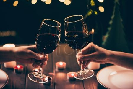Photo for Cropped shot of two women clinking glasses with wine over served table with lit candles - Royalty Free Image