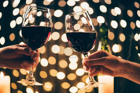 Photo for Cropped shot of two women clinking glasses with red wine in front of bokeh background - Royalty Free Image