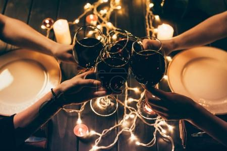 Photo for Cropped shot of four people clinking glasses with red wine over served table with fairylights decorations - Royalty Free Image