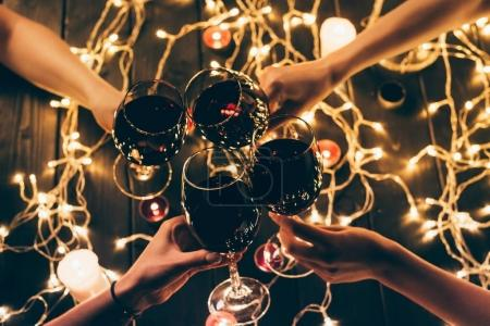 Photo for Cropped shot of four people clinking glasses with red wine over wooden table with fairylights decorations - Royalty Free Image