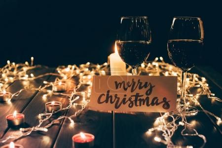 glasses with wine and merry christmas card
