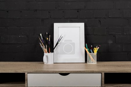 Photo for Close up view of empty photo frame, paintbrushes and office supplies on table - Royalty Free Image