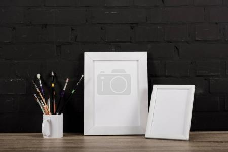 Photo frames and drawing equipment on table