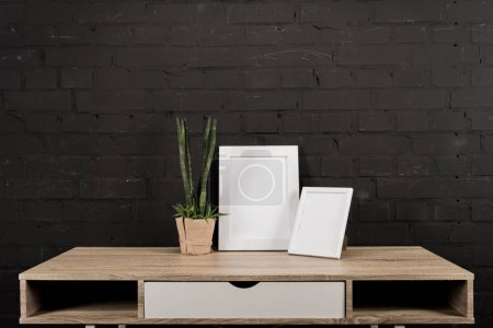 Photo for Close up view of empty photo frames and plant in flowerpot on wooden table - Royalty Free Image