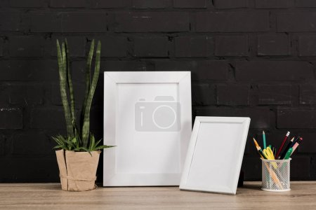 Photo for Close up view of empty photo frames, pencils and plant in flowerpot on tabletop - Royalty Free Image