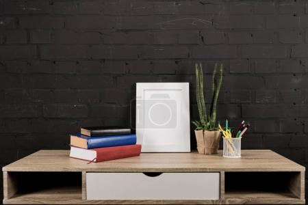 Photo frame and plant in flowerpot on table