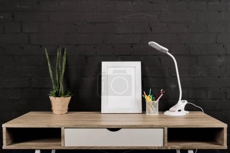 cadre photo et lampe de table sur le lieu de travail