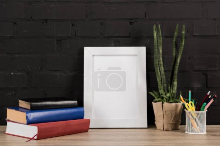 Photo for Close up view of photo frame, office supplies, plant in flowerpot and books on wooden tabletop - Royalty Free Image