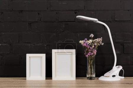 Photo for Close up view of empty photo frames, flowers in vase and table lamp on wooden table - Royalty Free Image