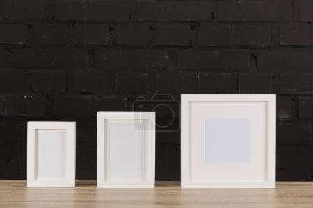 empty photo frames on wooden tabletop