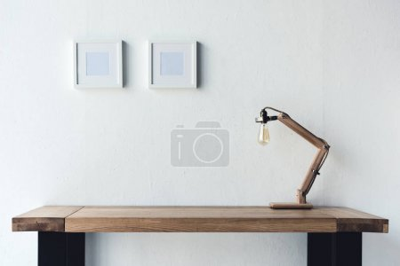 Photo for Close up view of empty photo frames hanging on wall at workplace with table lamp - Royalty Free Image