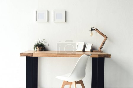 Photo for Empty photo frames hanging on wall at workplace with chair near by - Royalty Free Image