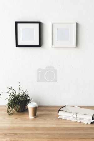 Photo for Close up view of empty photo frames hanging on wall at workplace with coffee to go in room - Royalty Free Image