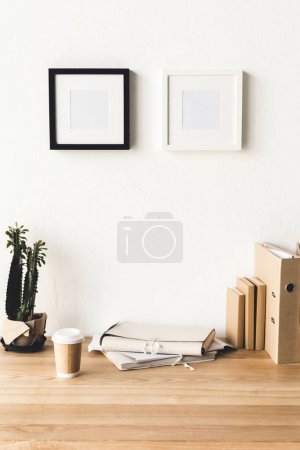 Photo for Close up view of empty photo frames hanging on wall at workplace with office supplies and coffee to go in room - Royalty Free Image
