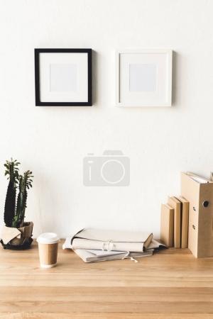 Photo pour Bouchent la vue de cadres de photo vide accroché au mur près du milieu de travail avec les fournitures de bureau et de café pour aller dans la chambre - image libre de droit