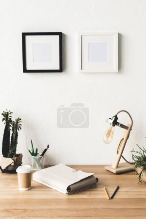 Photo for Close up view of empty photo frames hanging on wall at workplace with folder and table lamp in room - Royalty Free Image