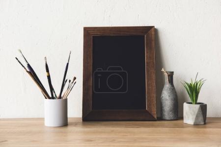 Photo pour Vue rapprochée du cadre photo vide, du vase et des pinceaux sur la table en bois - image libre de droit