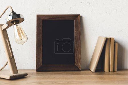 Photo pour Vue rapprochée du cadre photo vide et de la lampe de table sur le lieu de travail - image libre de droit
