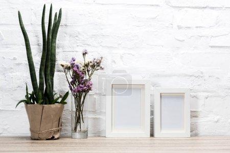 Foto de Cerrar vista de marcos de fotos vacíos y flores sobre mesa de madera - Imagen libre de derechos