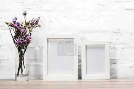 Photo for Close up view of empty photo frames and flowers in vase - Royalty Free Image