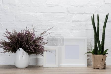 Photo for Close up view of empty photo frames and flowers on wooden tabletop - Royalty Free Image
