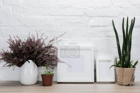 Foto de Cerrar vista de flores y marcos vacíos en el tablero de madera - Imagen libre de derechos