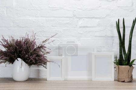 Photo for Close up view of empty photo frames and flowers on tabletop - Royalty Free Image