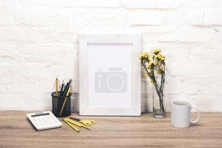 Photo pour Vue rapprochée du cadre photo vide, fournitures de bureau, tasse à café et fleurs dans un vase sur la table - image libre de droit