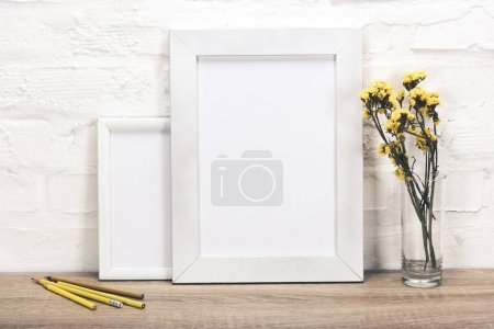 Photo for Close up view of empty photo frames, pencils and flowers in vase on wooden surface - Royalty Free Image