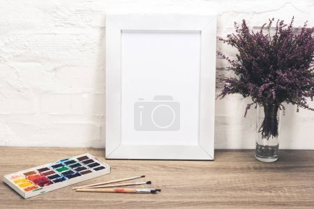 Photo for Close up view of photo frame, lavender flowers in vase and drawing equipment on wooden tabletop - Royalty Free Image